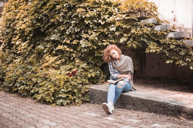 Frau, die an bord sitzt und buch nahe pflanze liest Kostenlose Fotos