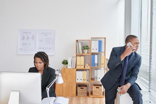 Frau, die an computer und geschäftsmann sprechen am telefon im büro arbeitet Kostenlose Fotos