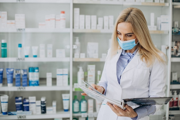 Frau, die an der apotheke arbeitet und mantel trägt Kostenlose Fotos