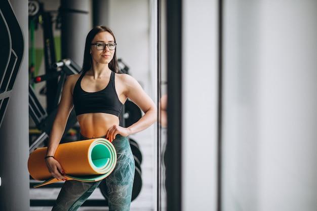 Frau, die an der turnhalle hält yogamatte ausübt Kostenlose Fotos
