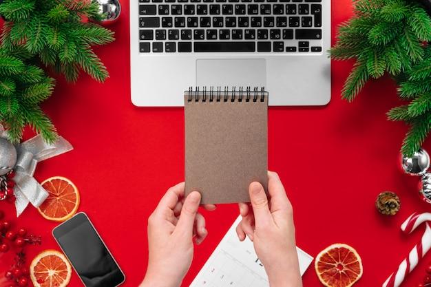 Frau, die an einem bürotisch mit weihnachtsfestlichen dekorationen arbeitet Premium Fotos