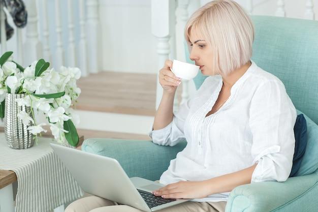 Frau, die an einem laptop arbeitet und kaffee trinkt Premium Fotos