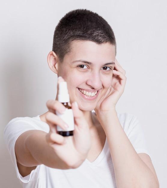 Frau, die an hand kamera mit hautprodukt betrachtet Kostenlose Fotos