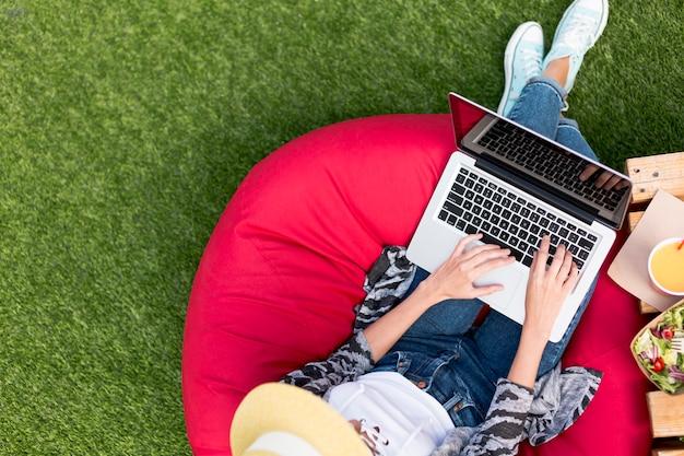 Frau, die an laptop arbeitet und salat isst Kostenlose Fotos