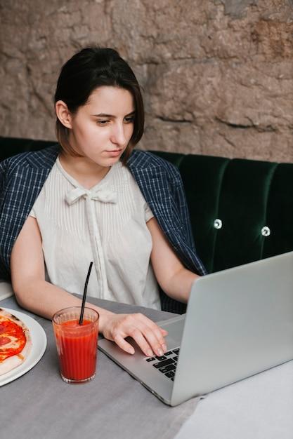 Frau, die an laptop im café arbeitet Kostenlose Fotos