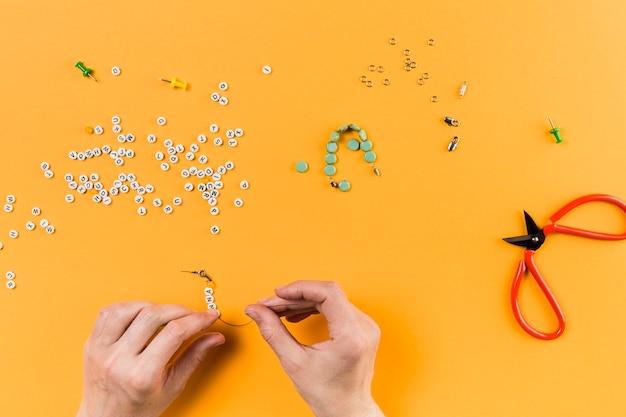 Frau, die armband von den buchstabeperlen auf gelbem hintergrund macht Kostenlose Fotos
