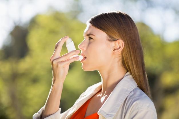 Frau, die asthmainhalator verwendet Premium Fotos