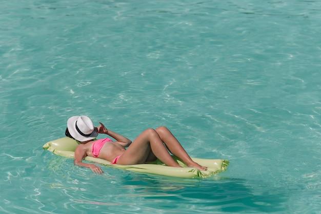 Frau, die auf aufblasbarer luftmatratze am türkiswasser sich entspannt Premium Fotos