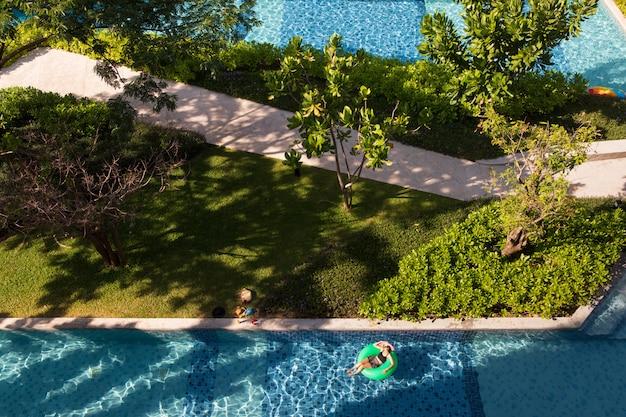 Frau, die auf ballon im swimmingpool legt Premium Fotos