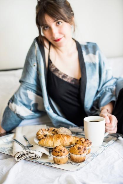 Frau, die auf bett frühstückt | Kostenlose Foto