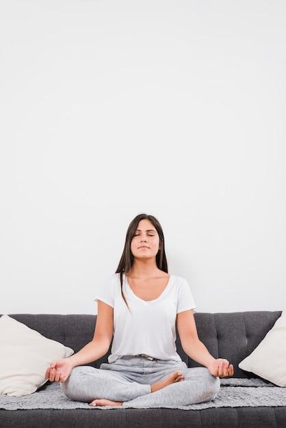 Frau, die auf bett meditiert Kostenlose Fotos