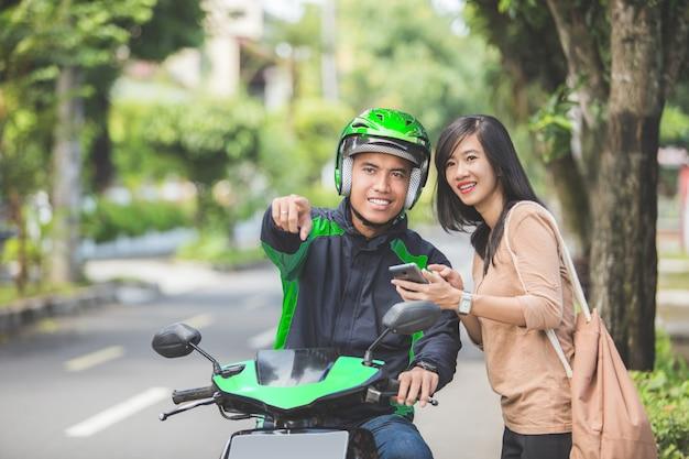 Frau, die auf bürgersteig spricht und motorradtaxi bestellt Premium Fotos