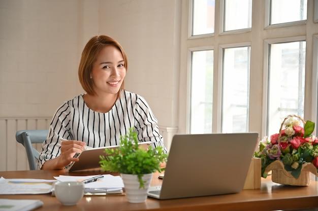 Frau, die auf bürotisch mit benetzendem dokumentenpapier sitzt. Premium Fotos