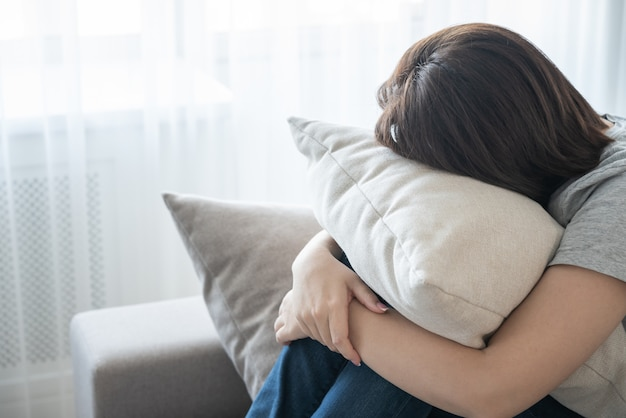 Frau, die auf couch sitzt und ein kissen-, einsamkeits- und traurigkeitskonzept umarmt Premium Fotos