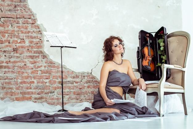 Frau, die auf dem boden nahe dem stuhl mit violine sitzt Premium Fotos