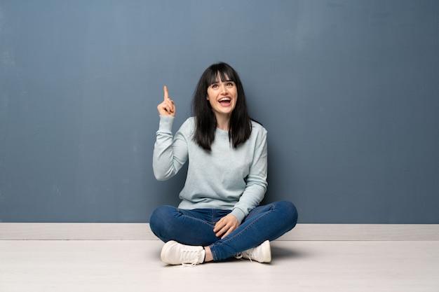 Frau, die auf dem boden sitzt, der beabsichtigt, die lösung beim anheben eines fingers zu verwirklichen Premium Fotos