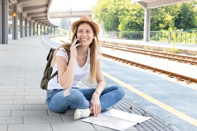 Frau, die auf dem boden sitzt und spricht Kostenlose Fotos