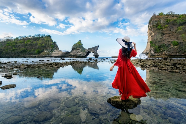 Frau, die auf dem felsen am atuh-strand, nusa penida insel in bali, indonesien steht Kostenlose Fotos