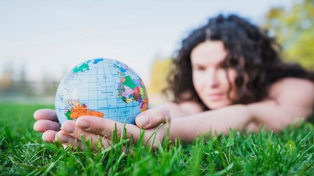 Frau, die auf dem grünen gras hält kugel in der hand über grünem gras liegt Kostenlose Fotos
