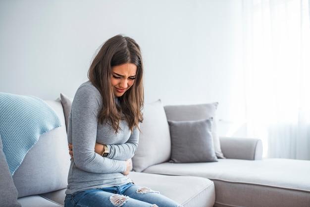 Frau, die auf dem sofa schaut krank im wohnzimmer liegt Premium Fotos