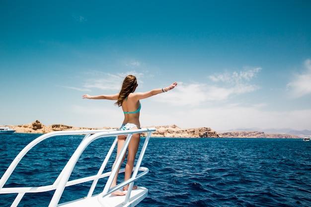 Frau, die auf der nase der yacht an einem sonnigen sommertag steht, brise, die haare entwickelt, Kostenlose Fotos