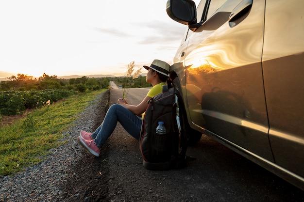 Frau, die auf der straße bei sonnenuntergang mit autos und rucksäcken sitzt konzept von ferien und von reise Premium Fotos