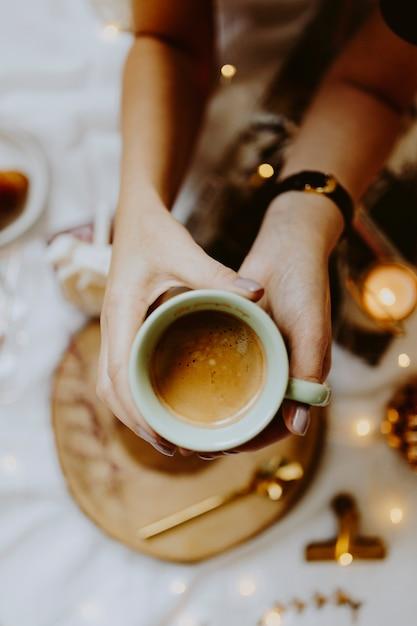 Frau, die auf einem bett sitzt und einen tasse kaffee zeigt Premium Fotos