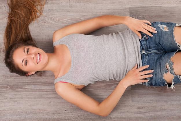 Frau, die auf einem fußboden mit kopfhörern liegt Kostenlose Fotos