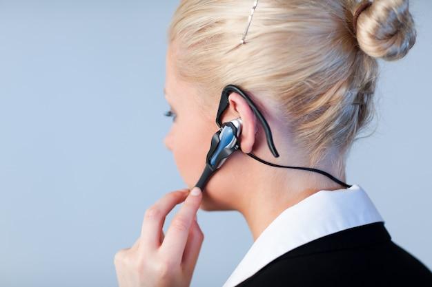 Frau, die auf einem kopfhörer mit fokus auf kopfhörer spricht Premium Fotos