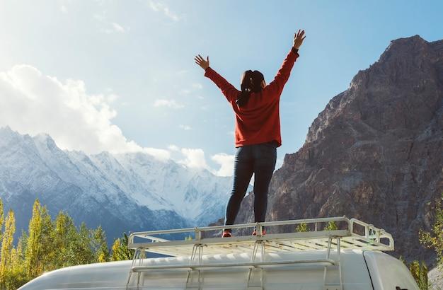 Frau, die auf einem packwagen steht, der den schönen berg gegenüberstellt Premium Fotos