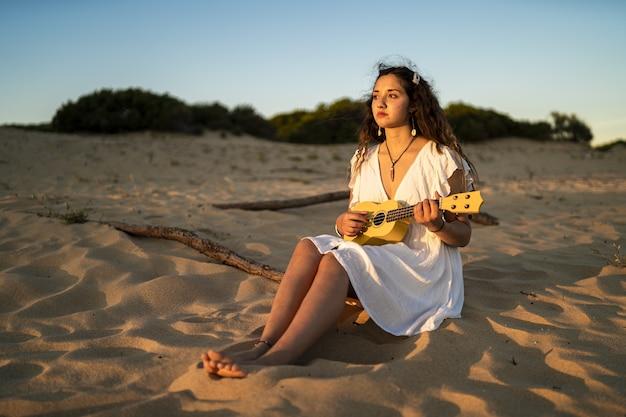 Frau, die auf einem sandigen boden sitzt, während sie eine gelbe ukulele am strand spielt Kostenlose Fotos