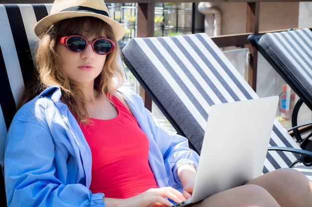 Frau, die auf einem sonnenruhesessel sich entspannt Premium Fotos
