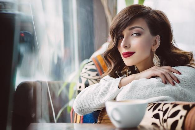 Frau, die auf einem stuhl in einem café stationiert Kostenlose Fotos