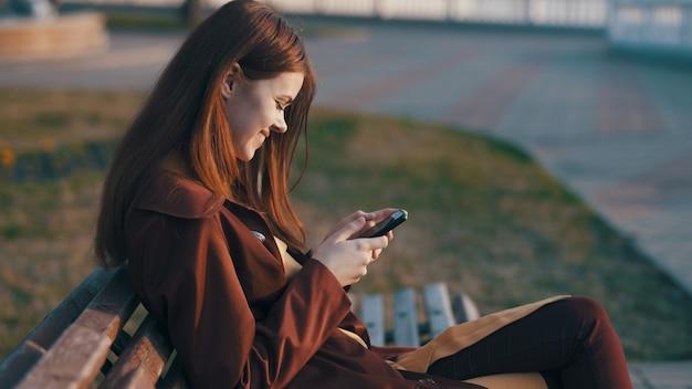 frau die auf einer bank in einem park herbst sitzt