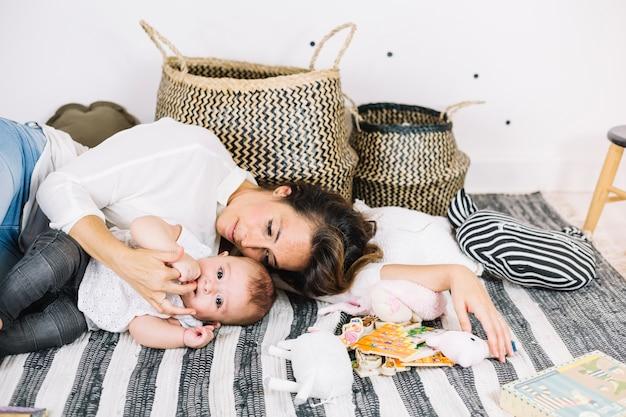 Frau, die auf gestreiftem lappen mit schätzchen liegt Kostenlose Fotos