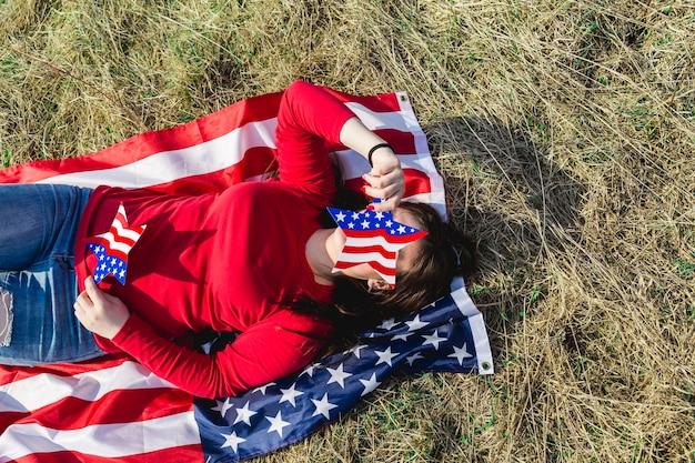 Frau, die auf gewebe der amerikanischen flagge auf feld liegt Kostenlose Fotos