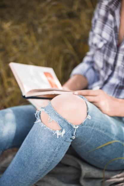 Frau, die auf gras mit buch in beunruhigten jeans sitzt Kostenlose Fotos