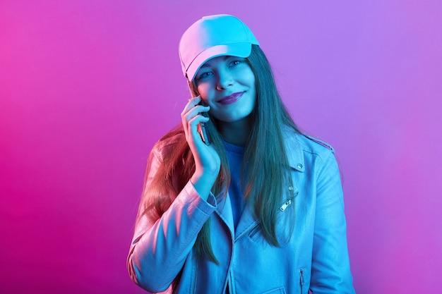 Frau, die auf handy spricht, während sie gegen rosa neonwand steht Premium Fotos