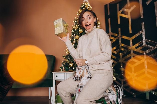 Frau, die auf hölzernem ponystuhl durch den weihnachtsbaum sitzt Kostenlose Fotos