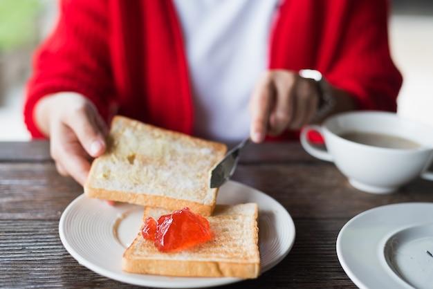 Frau, die auf hölzerner tabelle frühstückt Premium Fotos