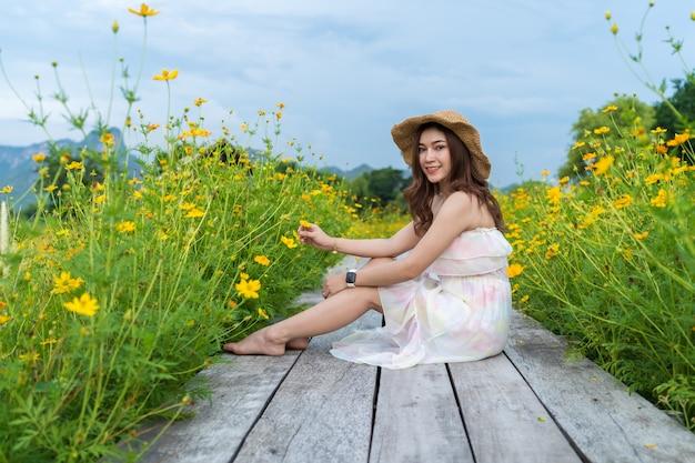 Frau, die auf holzbrücke mit gelbem kosmosblumenfeld sitzt Premium Fotos