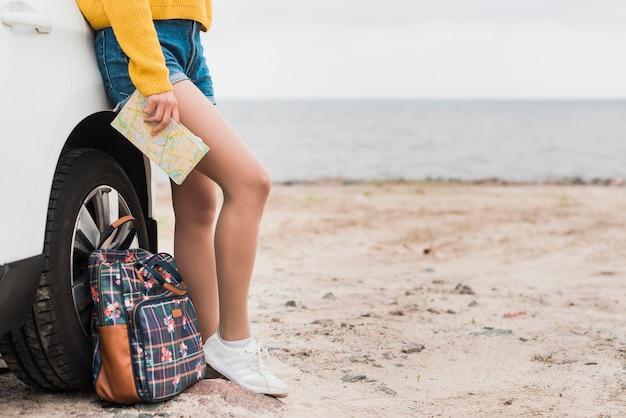Frau, die auf ihrem auto am strand sich lehnt Kostenlose Fotos