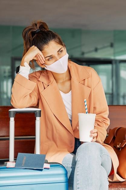 Frau, die auf ihrem gepäck ruht, während sie medizinische maske am flughafen während der pandemie trägt Kostenlose Fotos