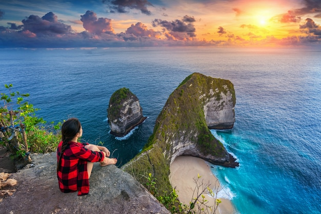 Frau, die auf klippe sitzt und sonnenuntergang am kelingking-strand in nusa penida insel, bali, indonesien betrachtet Kostenlose Fotos