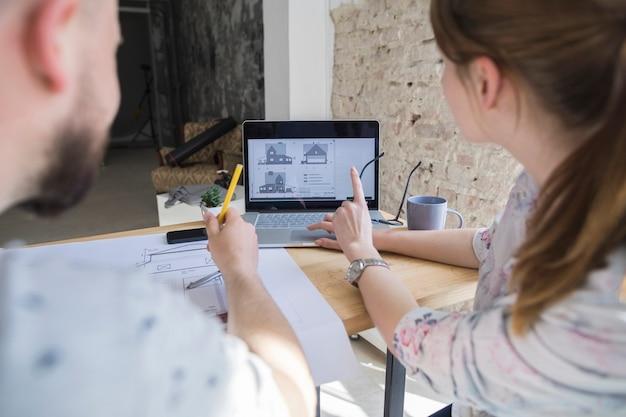 Frau, die auf laptopschirm beim arbeiten mit ihrem kollegen am arbeitsplatz zeigt Kostenlose Fotos
