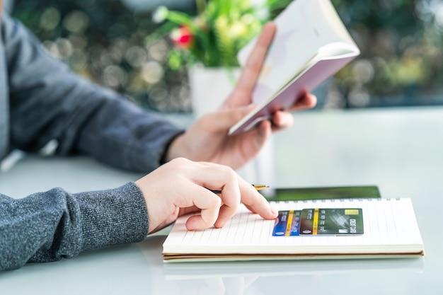 Frau, die auf notizbuch mit kreditkarte und smartphone-schreibtisch schreibt Premium Fotos