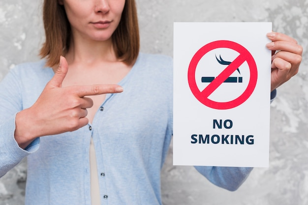Frau, die auf papier mit nichtraucherzeichen und text zeigt Kostenlose Fotos