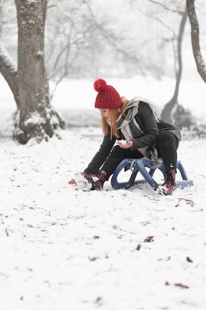 Frau, die auf pferdeschlitten sitzt und mit schnee spielt Kostenlose Fotos