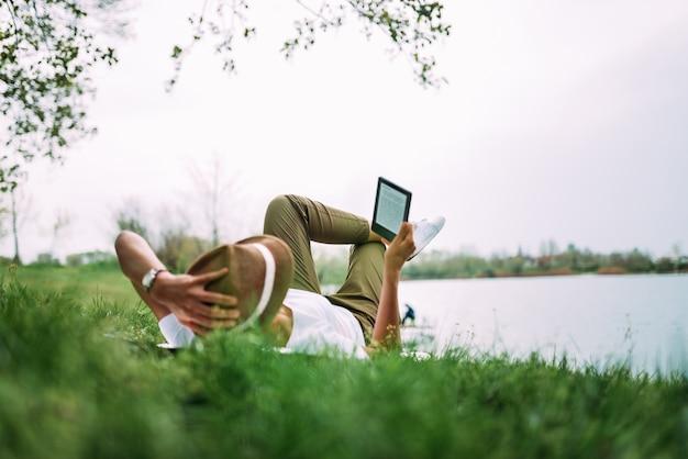 Frau, die auf rasenfläche legt und e-buch liest. Premium Fotos