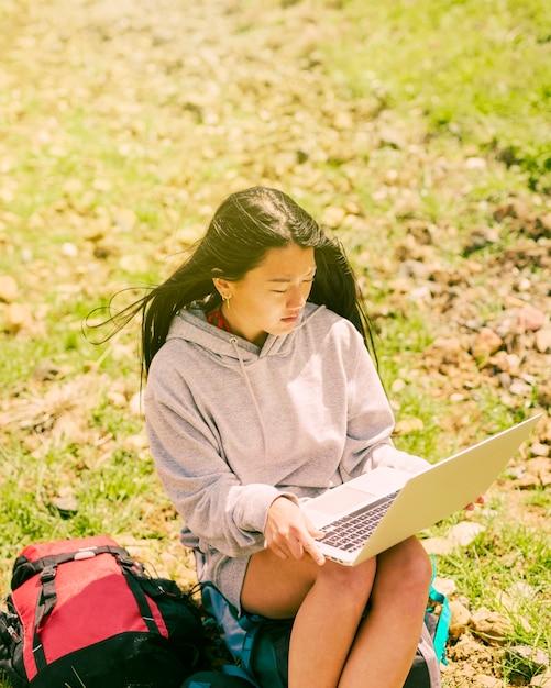 Frau, die auf rucksack sitzt und im laptop arbeitet Kostenlose Fotos